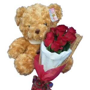 Traditional brown Teddy Bear together with a bunch of Red Rose, close up