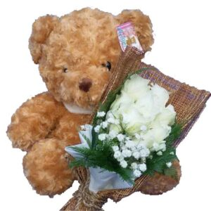 Traditional brown Teddy Bear together with a bunch of White Rose, close up
